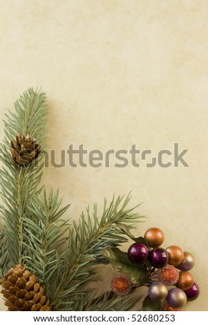 Christmas corner frame with fir branch, holly berry accent, and copyspace on antique style paper - stock photo