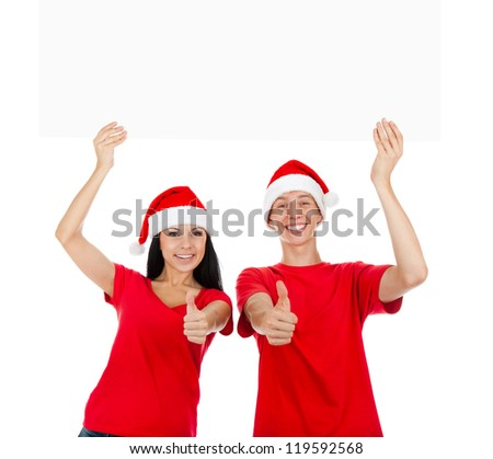 Christmas couple hold thumb up gesture white board with empty copy space, concept of advertise new year season shopping sale, wear red hats and shirts, isolated over white background - stock photo