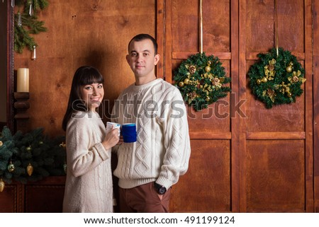Christmas couple holding cups in knitted covers
