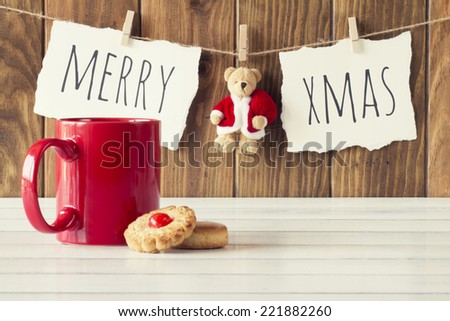 "Christmas cozy scene: a red mug and some shortbread on a white wooden table. ""Merry xmas"" and a Teddy bear with Santa Claus dress is hanging on a rope with clothespins. Vintage Style. - stock photo"