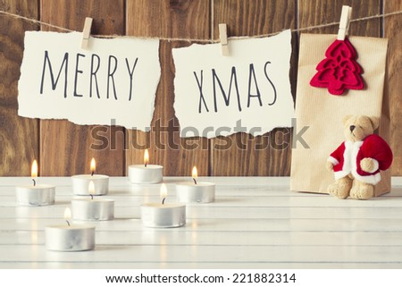 "Christmas cozy scene: some candles, a gift and a Teddy bear with Santa Claus dress on a white wooden table. ""Merry xmas"" is hanging on a rope with clothespins. Vintage Style. - stock photo"