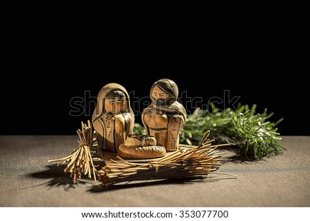 Christmas Crib. Figures of Baby Jesus, Virgin Mary and St. Joseph over a black background - stock photo