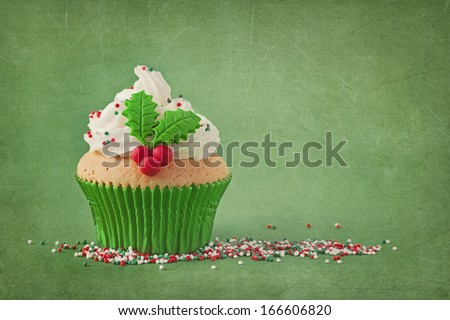 Christmas cup cakes with holly berry on a green background - stock photo