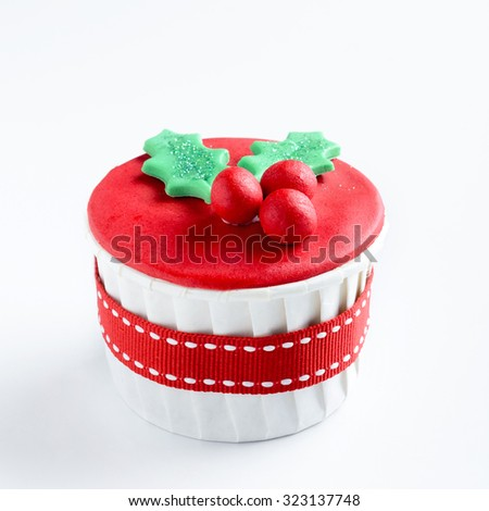 Christmas cupcake in traditional red green colors with mistletoe, decorative element - stock photo