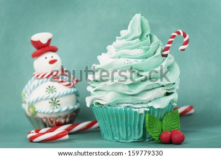 Christmas cupcake with candy cane and snowman - stock photo