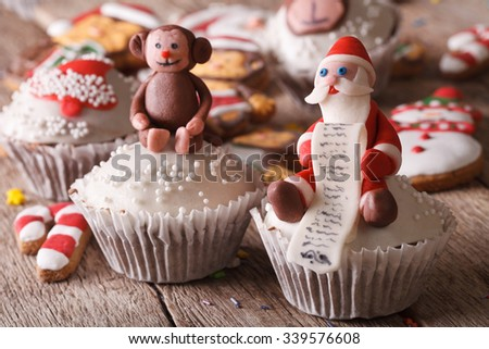 Christmas cupcakes decorated with figures of Santa and monkey close-up on a wooden table. horizontal - stock photo