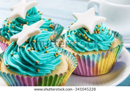 Christmas cupcakes with a star on the wooden table. focus on the edges cupcakes, mid frame - stock photo