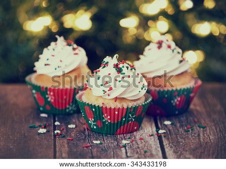 Christmas cupcakes with vanilla frosting and red and green sprinkles on rustic table. Shallow depth of field. Sparkling holiday lights background. Vintage filter effects. - stock photo