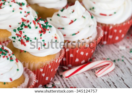 Christmas cupcakes with vanilla frosting and red and green sprinkles on wooden table with a candy cane. Shallow depth of field.