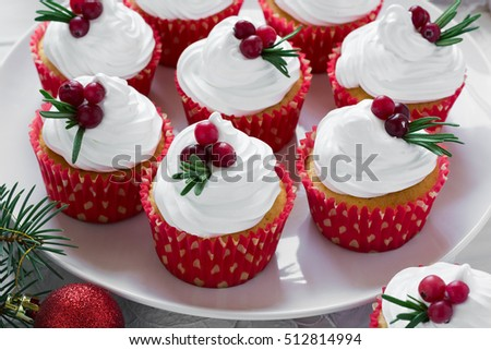 Christmas cupcakes with vanilla frosting, cranberries and rosemary on white wooden background. Selective focus