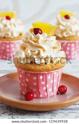 Christmas cupcakes with whipped cream topping and cranberrieson . Christmas festive food dessert.