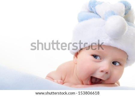 christmas cute baby boy lying on blue soft plaid like on snowdrift, beautiful funny infant in Santa's hat - stock photo