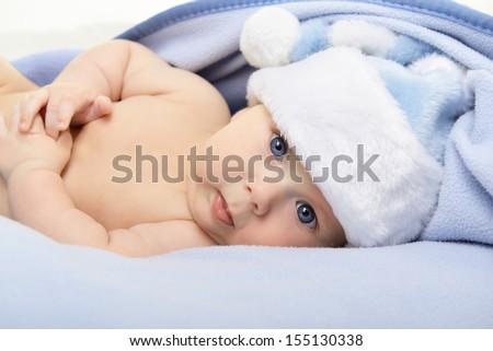 christmas cute baby boy lying on blue soft plaid like on snowdrift, beautiful infant in Santa's hat - stock photo