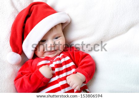 christmas cute smiling baby boy lying on soft plaid, beautiful funny infant in Santa's hat - stock photo