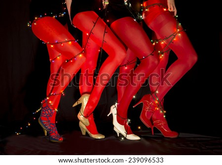 Christmas dancers. Group of professional female cabaret dancers with Christmas lights tied around legs
