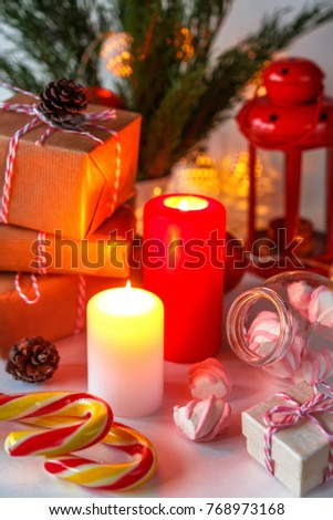 Christmas decor of a candle, gifts, marshmallow in a festive atmosphere background with copy space