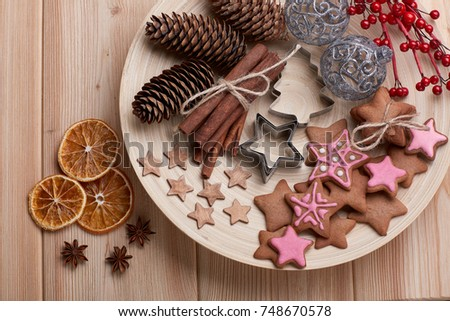 Christmas decor with gingerbreads lying on a wooden plate on a wooden background. Top view. For greeting card.