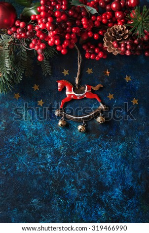 Christmas decor with horse and winter berries - stock photo