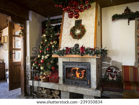 Christmas decorated burning fireplace with christmas tree - stock photo