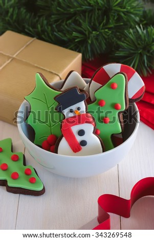 Christmas decorated cookies in small bowl on white wooden background - stock photo