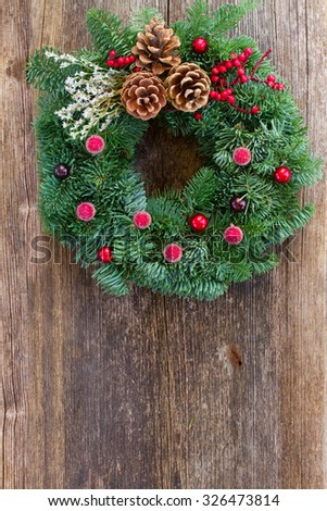 christmas decorated evergreen  wreath  on  aged wooden  background