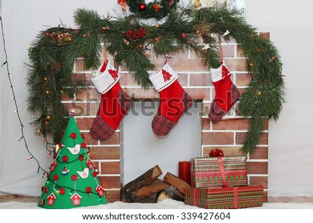Christmas decorated fireplace with three different size Santa socks and handmade New Year tree, winter holiday concept