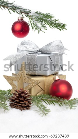 Christmas Decoration - a branch, a present and some baubles on a white background - stock photo