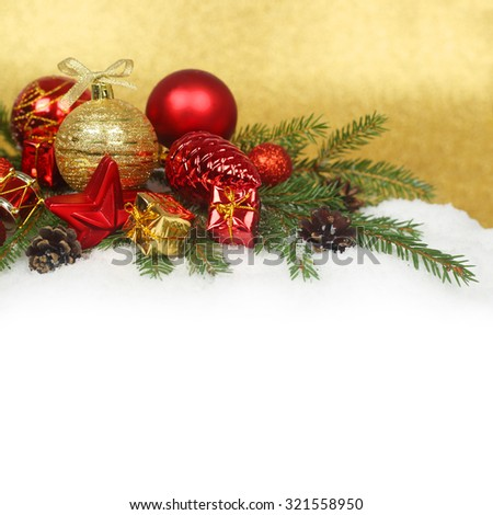 Christmas decoration and fir branches with pine cones on snow - stock photo