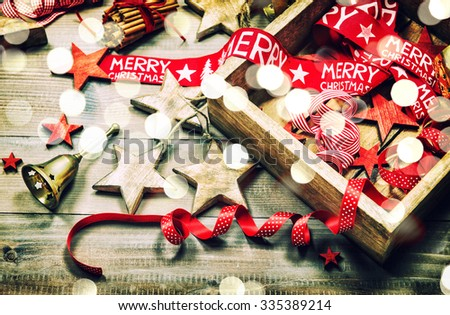 Christmas decoration and ornaments on rustic wooden background. Retro style dark colored picture with light effects - stock photo