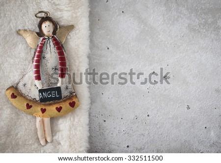 Christmas decoration, angel on plush, concrete, copy space - stock photo