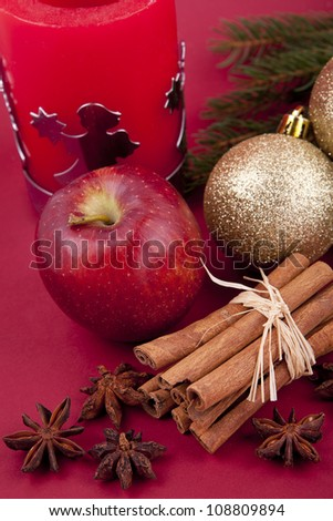 christmas decoration aromatic red apple, cinnamon, anise and tree on red background
