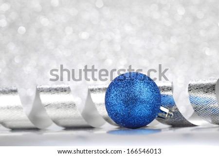 Christmas decoration ball and ribbon on silver glitter background