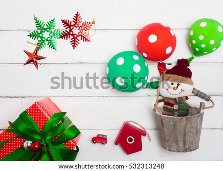 Christmas decoration balloon, doll,gift,tree,cute object  on white wood  background . Red and gift box and decoration object  .top  view composition.