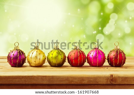 Christmas decoration balls on wooden table over green bokeh background - stock photo