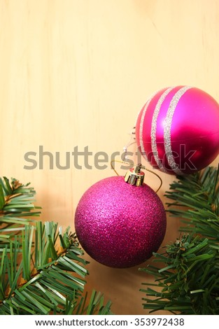 Christmas decoration (branch of spruce tree, pink and purple baubles) on the wooden background with copy space - stock photo