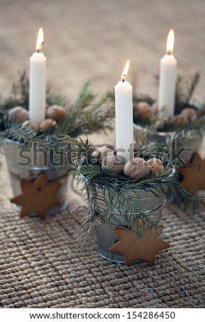 christmas decoration: Burning candle in metal flower pot with cookies with fir branches on beige background - stock photo