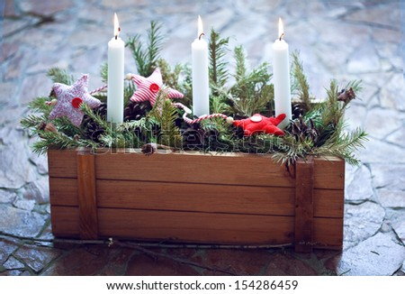 christmas decoration burning candles in a wooden box with fir branches and christmas fabric toys - Wooden Box Christmas Decorations