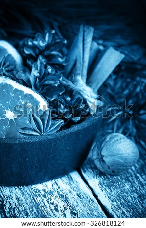 Christmas decoration card with evergreen fir tree, cones, cinnamon on rustic wooden background. Selective focus, toned inage, shallow dof - stock photo