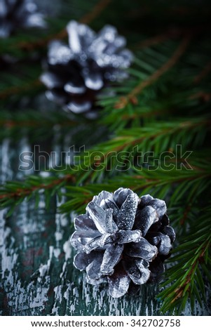 Christmas decoration card with  fir tree cones on rustic wooden background. Selective focus, shallow dof - stock photo