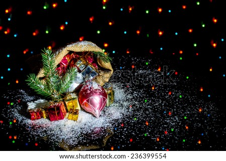Christmas decoration - Christmas bag with gifts on black background with colored lights
