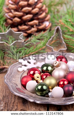 christmas decoration, christmas cookie cutters (star and christmas tree) with red, green, and white christmas balls on a silver plate with fir branches