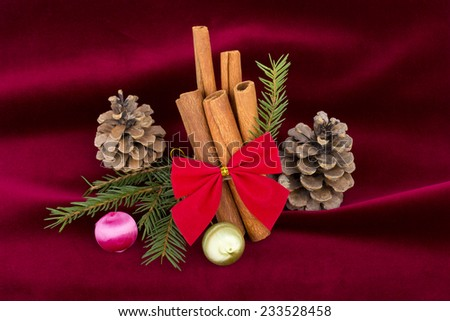 Christmas decoration - cinnamon sticks with red ribbon and globe, cones and fir branches on red velvet background - stock photo