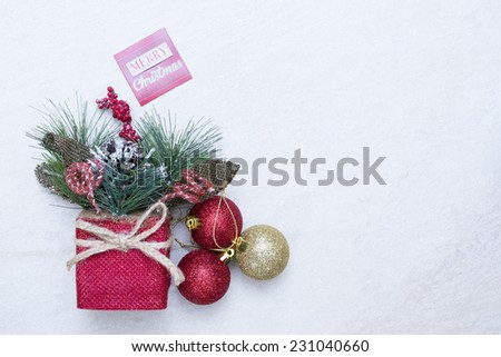 Christmas decoration consisting in arrangement of pine branch, pinecones, berries and red and golden balls with a merry christmas message isolated on a snow background - stock photo