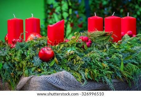 Christmas decoration evergreen wreath decorated with red candles - stock photo