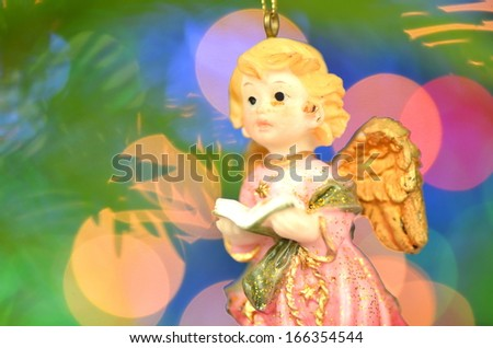 christmas decoration, figure of little angel singing carols against bokeh background - stock photo