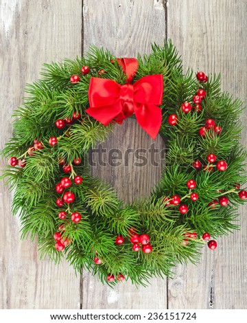 Christmas decoration fir wreath with red holly berries  on wood door surface  - stock photo