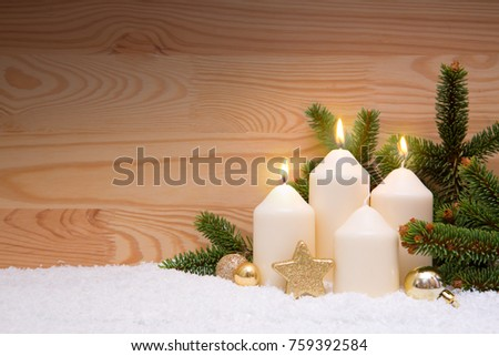 Christmas decoration for advent three candles burning. White burning Candles for the third advent. Third Advent.