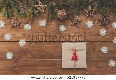 Christmas decoration, gift box and garland frame concept background, top view on wood table surface. Christmas ornaments and presents border with snowflakes and stars