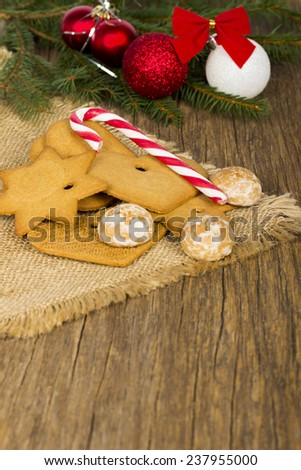 Christmas decoration - gingerbread and Christmas candy cane, balls and fir on old wooden background - stock photo
