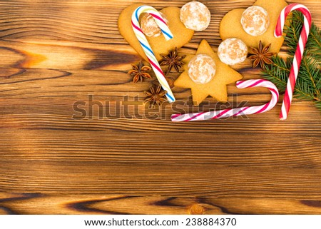 Christmas decoration - gingerbread, candy cane, star anise and fir branch on old wooden background - stock photo